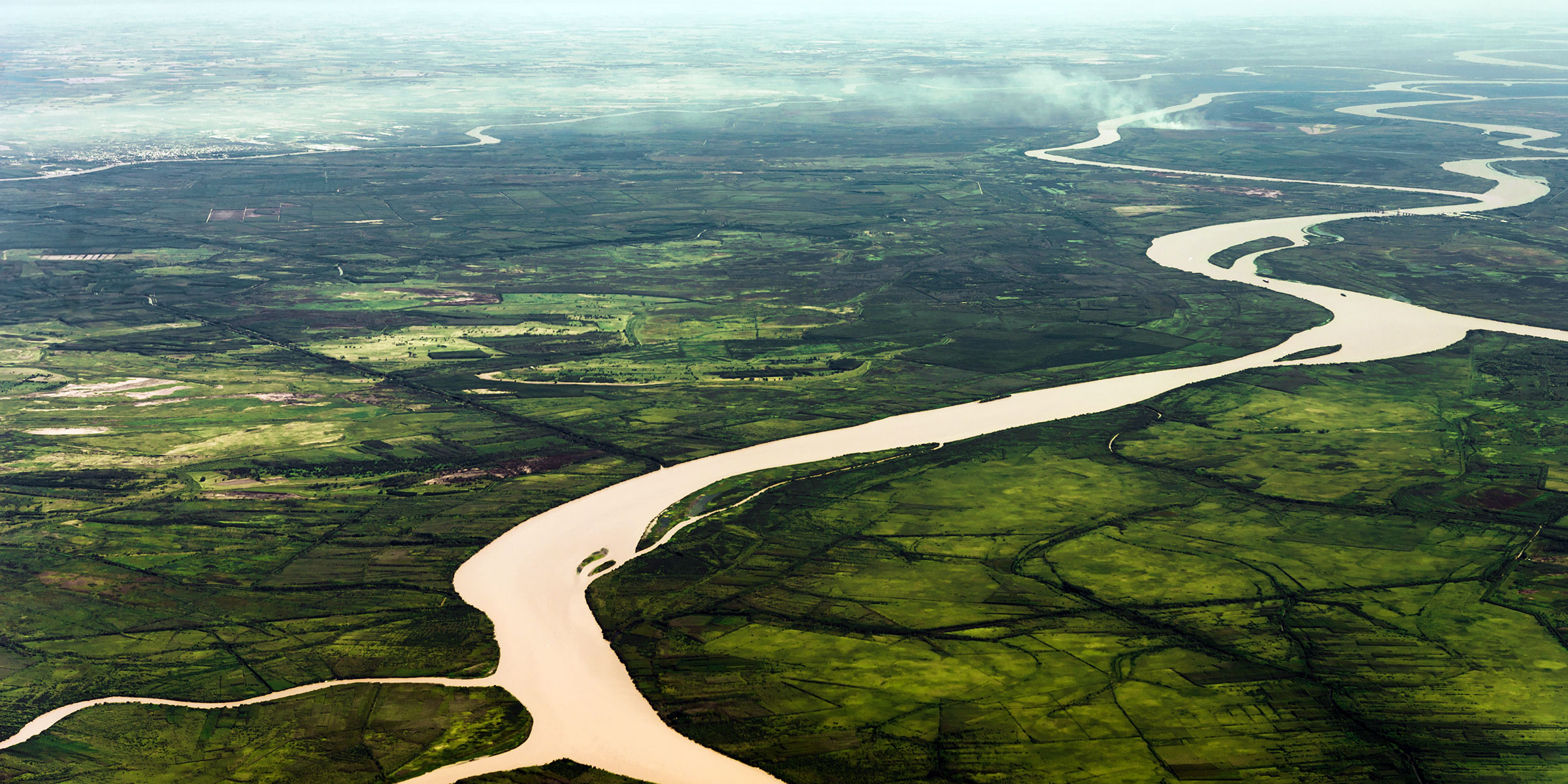 Aerial view of a silver river winding through fields and the Amazon rainforest